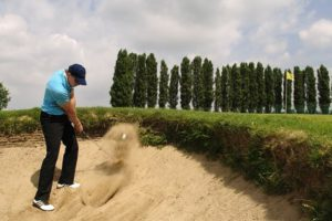 New to Golf - golfer in sand bunker